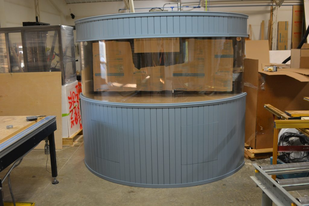 Painted slat style cabinetry for large half cylinder aquarium