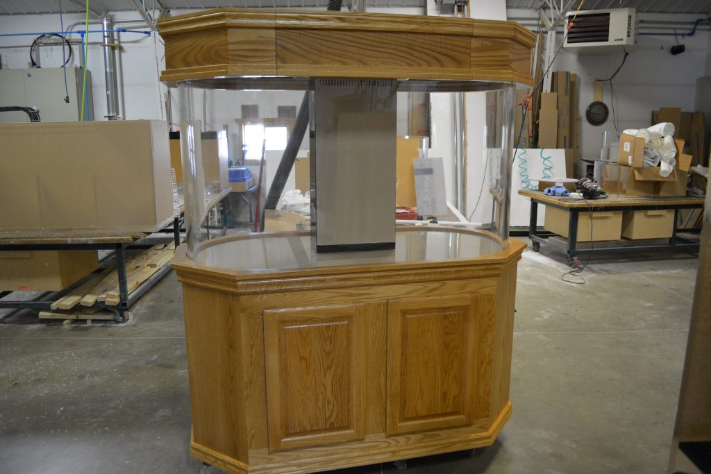 Flat panel oak cabinetry for double bullnose aquarium with raised panel doors