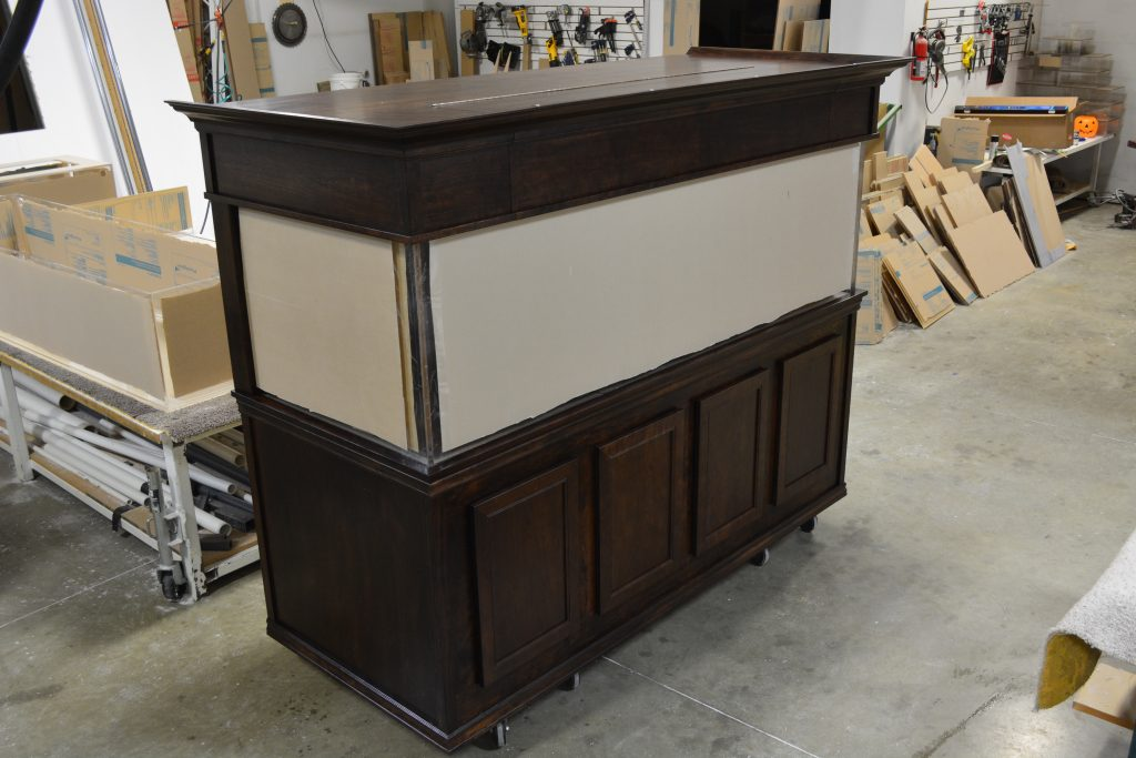 Stained deluxe walnut cabinetry with, flip front canopy, crown molding, and flat panel doors